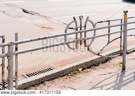 Broken Parts Of Abandoned Street Fence Near The Road. Poorness. Protection. Sidewalk. Pavement. Outd