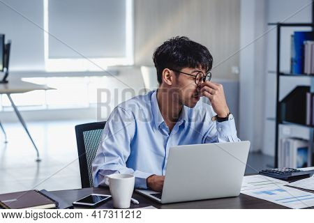 Asian Businessman Get Stress And Headache When Working With Laptop On Desk At Modern Office.business