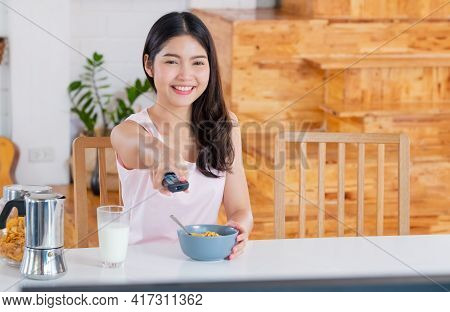 Asian Woman Wathcing Tv On Demand And Use Remote Control Change Television Channel At Breakfast In M