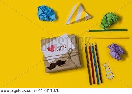 Gift Box With A Note Love You Dad On A Yellow Background With Pencils And Paper With Copy Space. Fla