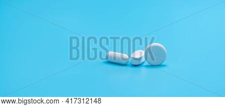 Round White Tablets Pills And Oval Tablets Pills On Blue Background. Pharmacy Shop Banner. Prescript