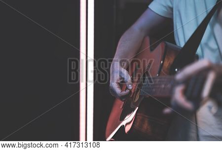 A Man Plays An Acoustic Guitar In A Room Copy Space. Live Performance, Acoustic Concert, Practice.