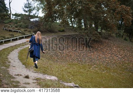 Girl Walks Along The Path In The Park Back View. Woman Goes Into The Distance Along The Autumn Alley