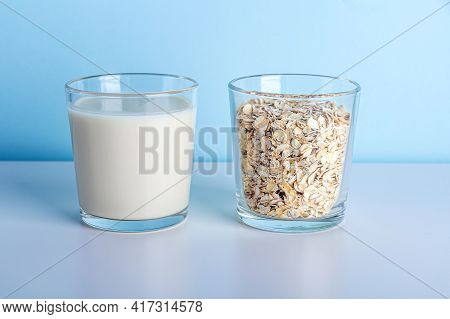 Glass Of Oat Vegetable Milk And Glass With Oat Flakes. Concept Of Making Plant Based Organic Veggie