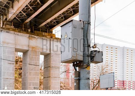 Electric Box With Wires Installed On Grey Pole In The City. Tall Building On The Background. Lightni