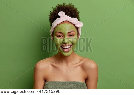 Optimistic Dark Skinned Woman With Curly Hair Wears Headband Applies Green Nourishing Mask For Skin