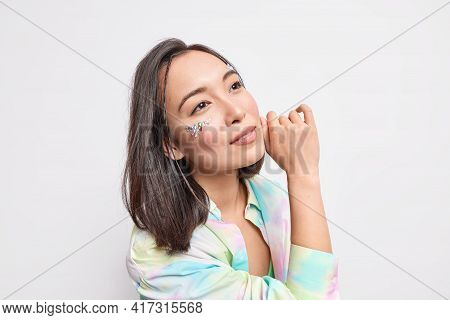 Cute Gorgeous Woman With Dark Hair Healthy Skin Touches Face Gently Has Shining Stones On Face Stand