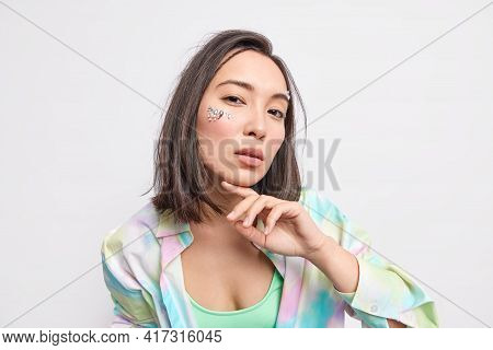 Horizontal Shot Of Serious Brunette Asian Woman Has Confident Face Decorated With Stones Touches Chi
