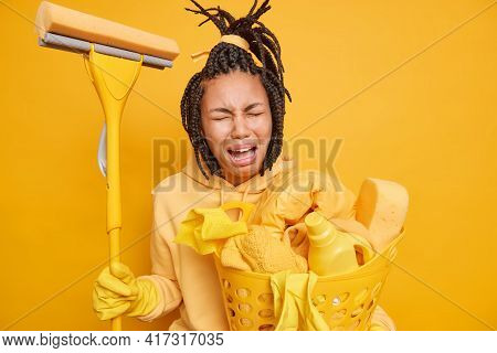 Dejected Dark Skinned Woman With Dreadlocks Cries From Tiredness Holds Mop And Laundry Basket Doesnt