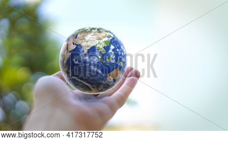 Human Hand Holds Small Earth With Care And Love. Planet Earth Globe Ball In Human Hand. Strong Human