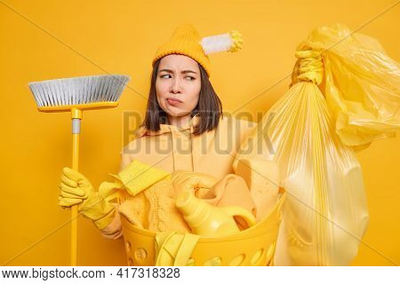 Housecleaning Service Concept. Displeased Asian Woman Looks At Polythene Bag Full Of Garbage Holds B