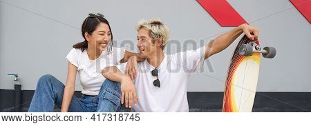 Asian Couple Resting After Skateboarding. A Young Man In A White T-shirt Held His Hand On The Surfsk