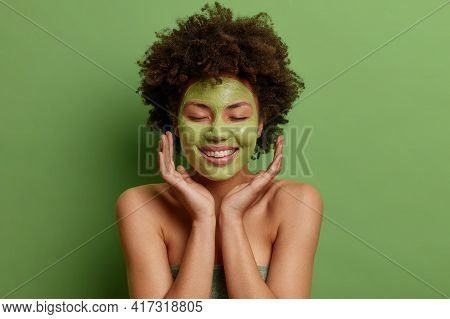 Skin Care And Beauty Treatments Concept. Pleased Afro American Woman Touches Face Gently Applies Gre