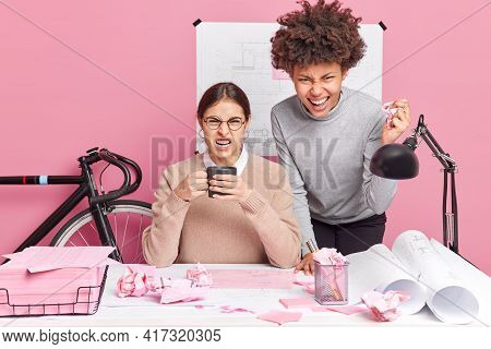 Photo Of Two Annoyed Multicultural Professional Women Smirk Faces Clench Teeth Look With Irritated E