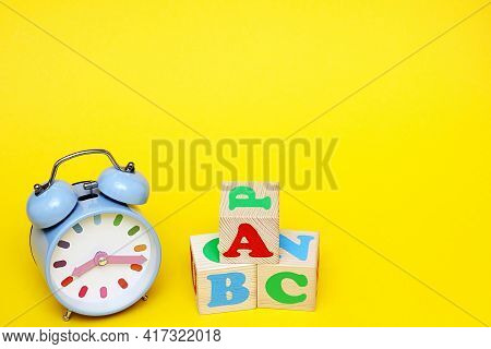 Abc -the First Letters Of The English Alphabet On Wooden Toy Cubes On A Yellow Background Next To Th