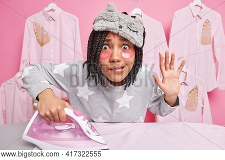 Housekeeping And Ironing Concept. Worried Afro American Woman With Dreadlocks Bites Lips Keeps Palm