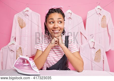 Cheerful Afro American Girl With Dreadlocks Leands At Ironing Board Smiles Broadly Looks Away Stroke