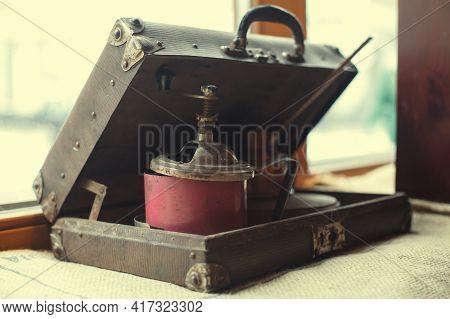 Old Coffee Grinder In Retro Suitcase On Burlap Fabric.