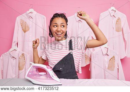 Carefree Cheerful Afro American Woman With Dreadlocks And Dark Skin Dances Near Ironing Board Keeps