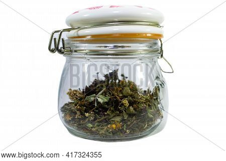 Dried Natural Tea Harvested From The Rich Transylvanian Meadows In A Glass Jar Isolated On White.