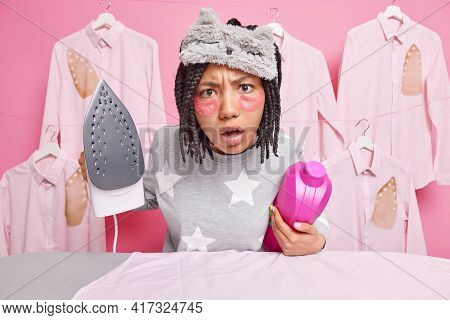Housework Laundry Housekeeping Concept. Indignant Dark Skinned Woman Applies Collagen Patches Under