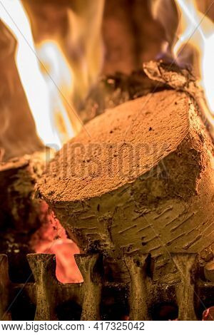 Winter Warmth. Wood Log Burning On An Open Fire. Close Up Of A  Silver Birch Log On A Fire Grate.