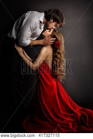 Sensual Couple Kissing In Love. Handsome Man Hugging Romantic Woman In Red Dress. Valentines People