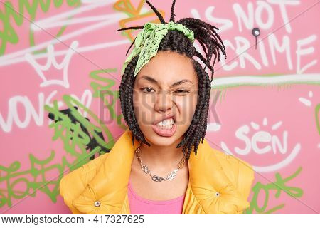 Teenage Lifestyle Concept. Cheeky Hipster Girl With Combed Dreadlocks Clenches Teeth Smirks Face Loo