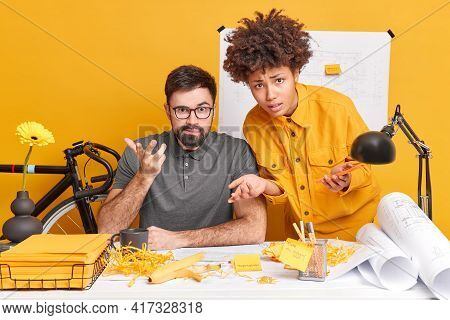 Puzzled Interracial Woman And Man Look Puzzled While Working In Office Draw Sketch Of Future Buildin