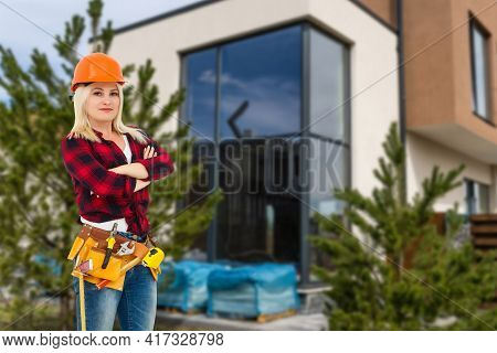 Happy Woman On The Background Of A New House. Portrait Of First Time Buyer, House Owner, Apartment R