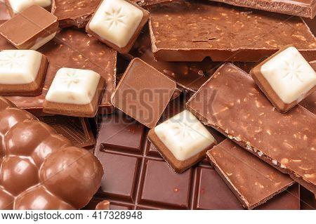 Close Up Chocolate. Top View Of Various Delicious Chocolate Pieces Background. Pieces Of Chocolate B