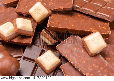 Top View Of Pieces Of Chocolate Bar With Chocolate Chips On Rustic Wooden Background. Milk Chocolate