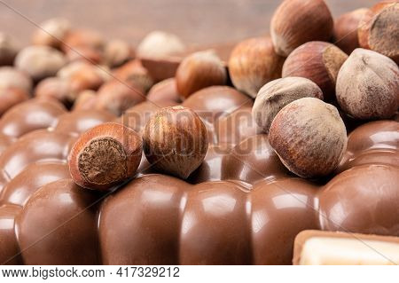 Chocolate Bars With Nuts. Pile Of Chocolate Pieces With Hazelnuts On Wooden Background. Different So