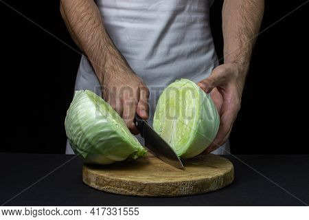 Cabbage On A Dark Background. The Cook Cuts The Cabbage On A Black Background. Young Fresh Cabbage.