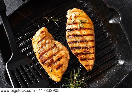 Grilled Chicken Breast Fillet On Grill Pan With Rosemary Close Up. Grilled Meat Steak On Rustic Blac
