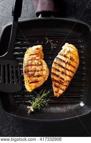 Grilled Chicken Breast Fillet On Grill Pan With Rosemary, Top View. Grilled Meat Steak On Rustic Bla