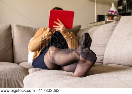A Portrait Of The Feet Of A Woman Sitting In A Cosy Couch In A Living Room Wearing A Blue Dress And