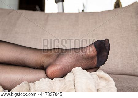 A Portrait Of The Legs And Feet Of A Woman In Black Nylon Pantyhose Or Stockings Lying On A Couch In