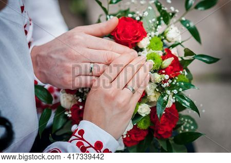Hands Of Newlyweds With Wedding Rings On A Wedding Bouquet
