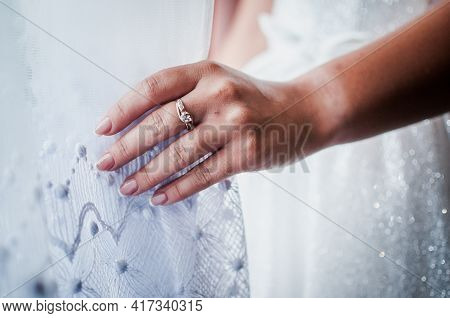 The Bride Holds A Gold Ring In Her Hands