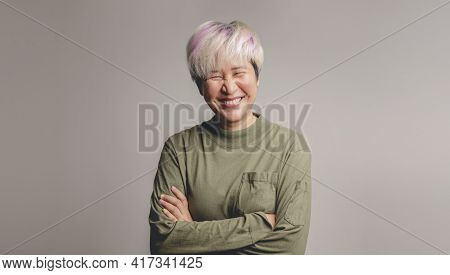 Portrait Of An Happy Asain Female. Smiling Woman With Stylish Hair. Crossed Arm With A Big Smile Aga