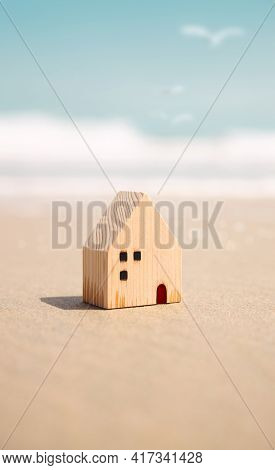 Beach House Concept. Mini Wooden House On The Sand Beach. Destination For Vacation Or Retirement Lif