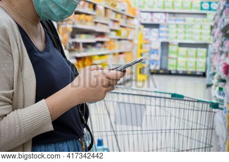 Young Woman Shopping In Supermarket With Trolley. Female Hands Using Smart Phone In Store. Woman Wea