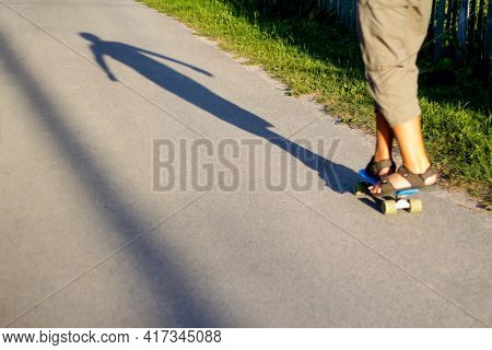 Defocus Little Child With Penny Skateboard On Path In Park. Boy Rides A Penny Board In Sunshine Day.