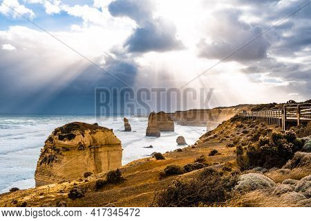 Sun Rays Through Clouds Shining On The Twelve Apostles Rock Formations On Great Ocean Road, Victoria