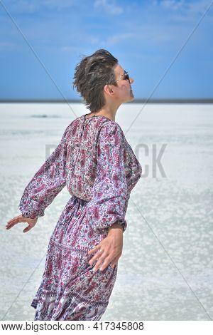 Woman In Dress On A White Salt Lake, Portrait Of A Woman On A White Salt Lake. Woman In Hat And Glas