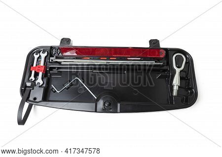 Warning Triangle, Wrench And Transportation Hook On A Black Cover For Car Repair On The Road In The