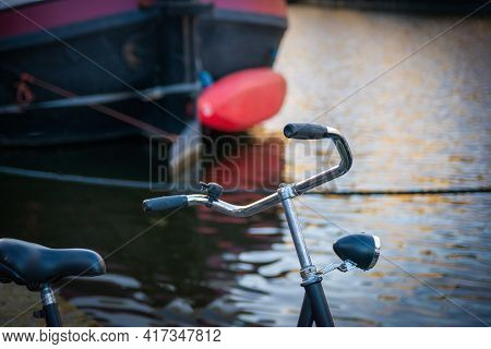 Traditional Dutch Ship, Canoe And Bicycle In The Harbour Of Leiden, Netherlands