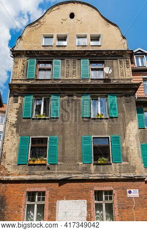 Walbrzych, Poland - June 15 2020: Facade Of Old Tenement House With Green Shutters Outside
