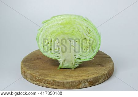 Cabbage On A White Background. Cabbage Cut In Half On A Light Background. Fresh Young Cabbage